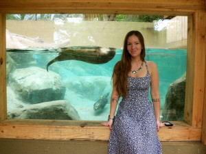 Woman standing in front of ottter aquarium