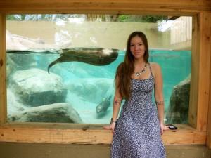 Woman standing in front of ottter aquarium