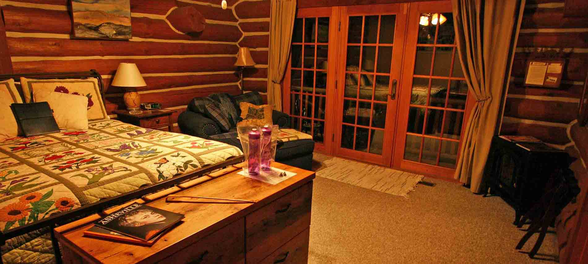Second floor rustic room with queen bed, fireplace, and french door leading onto a balcony with seating for two.