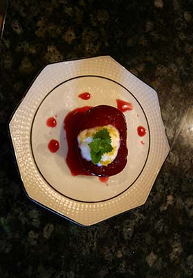 warm poached plum with yogurt, lemon zest and mint presented on white china plate.
