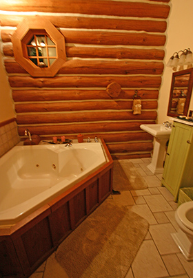 Two person Jacuzzi tub with log wall as the focal point and octogon window for filtered natural lighting.