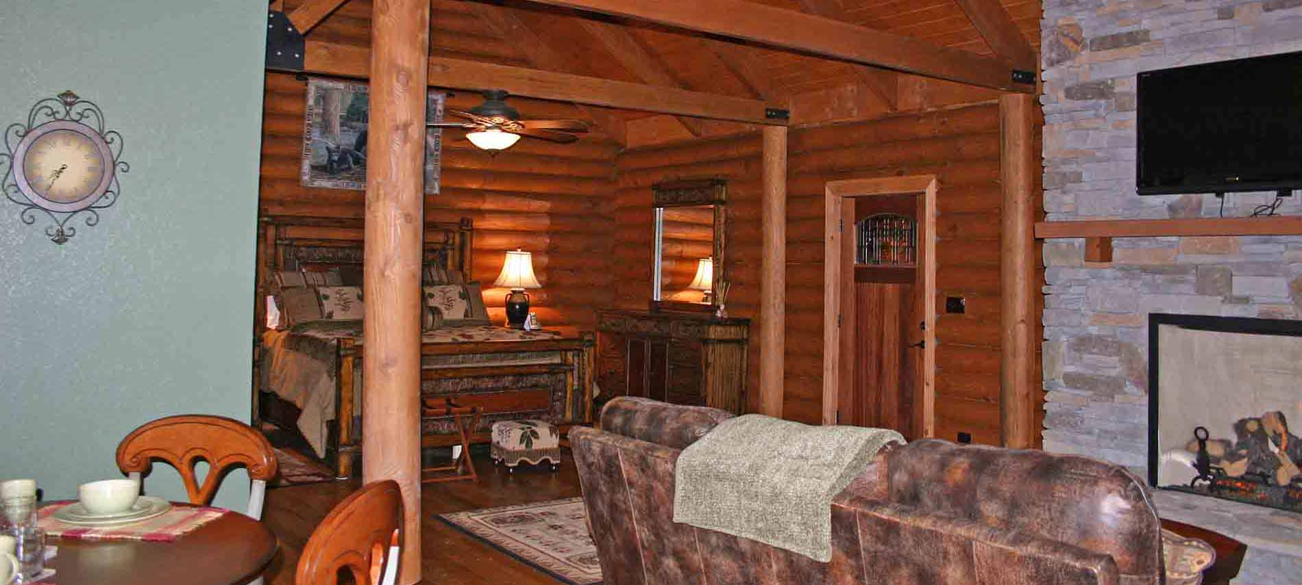 Log cabin Room with TV over stone fireplace beamed ceiling and dining table with leather couch