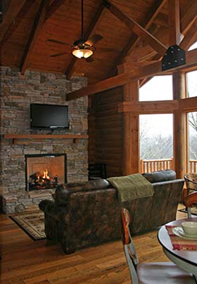 Fireplace with fire and TV above with deck on the right side