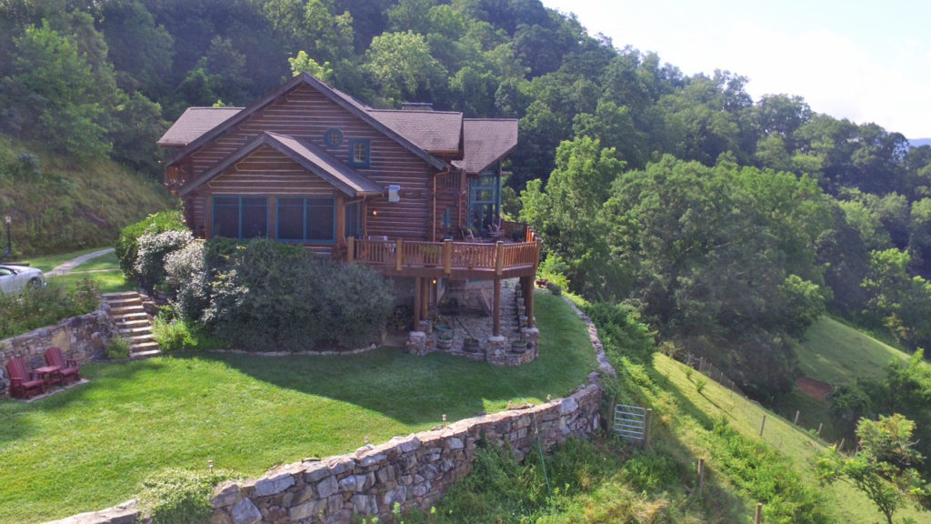 West side view of log lodge with rockers in lawn and side view of main deck and rock patio. The entrance walking path is to the left and the boulder retaining wall is on the right of the log lodge.
