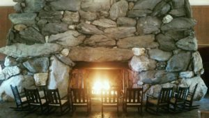View of stone fireplace with fire