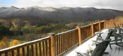 Snow covered deck overlooking green valley and snow-capped mountains.