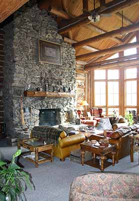 Greatroom view with Grand Stone fireplace and leather furniture for relaxing in front of the large widow