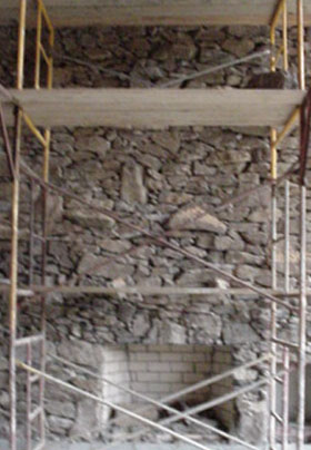 Stone Fireplace construction with scaffolding in great room