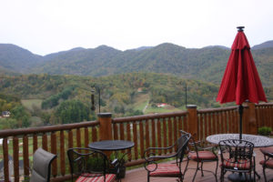 Mountains in distance that are still mostly green spotted with yellow and red fall foliage. foreground is deck with red umbrella and black iron table.
