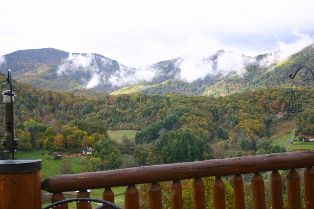 Puffy clouds in front of mountains with fall foliage colors of red, orange and yellow. Deck railing in foreground