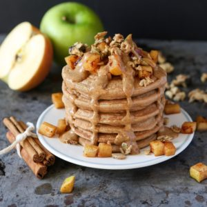 Stack of pancake topped with chopped apples and nuts, with a caramel-icing sauce dripping down the sides. Cinnamon sticks on side; 2 apples in back.