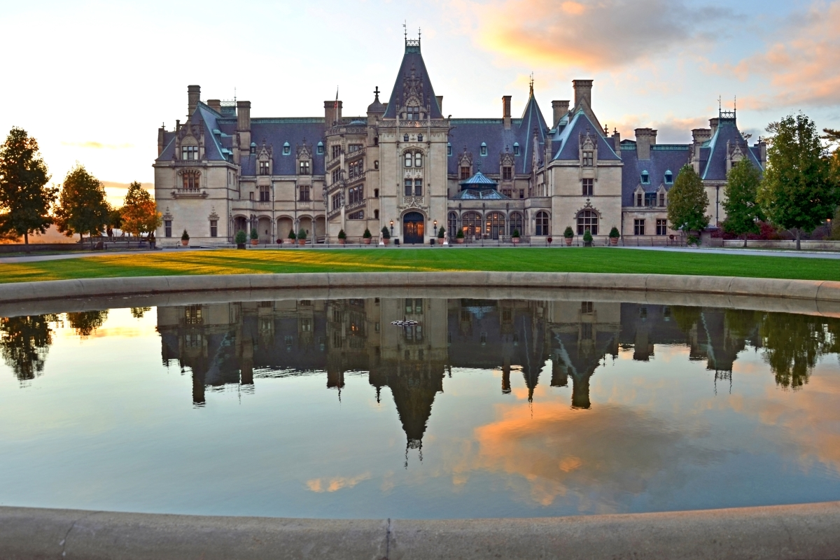 Biltmore Estate with reflecting pond in front, blue sky with one big orange-tinged cloud as background