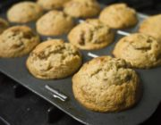 Muffins in an aluminum pan at an angle apparently coming out of the oven.