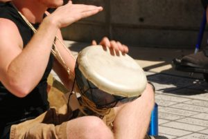 Male hands playing bongo on brick street