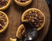 Wooden round tray holding 4 pecan tarts, 2 half visible, 1 cut into with black spoon.