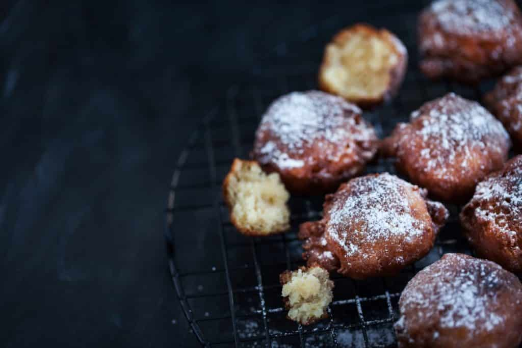 Dark fried apple fritters on right half of frame on dark background
