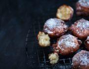 Dark fried apple fritters on right half of frame on dark background