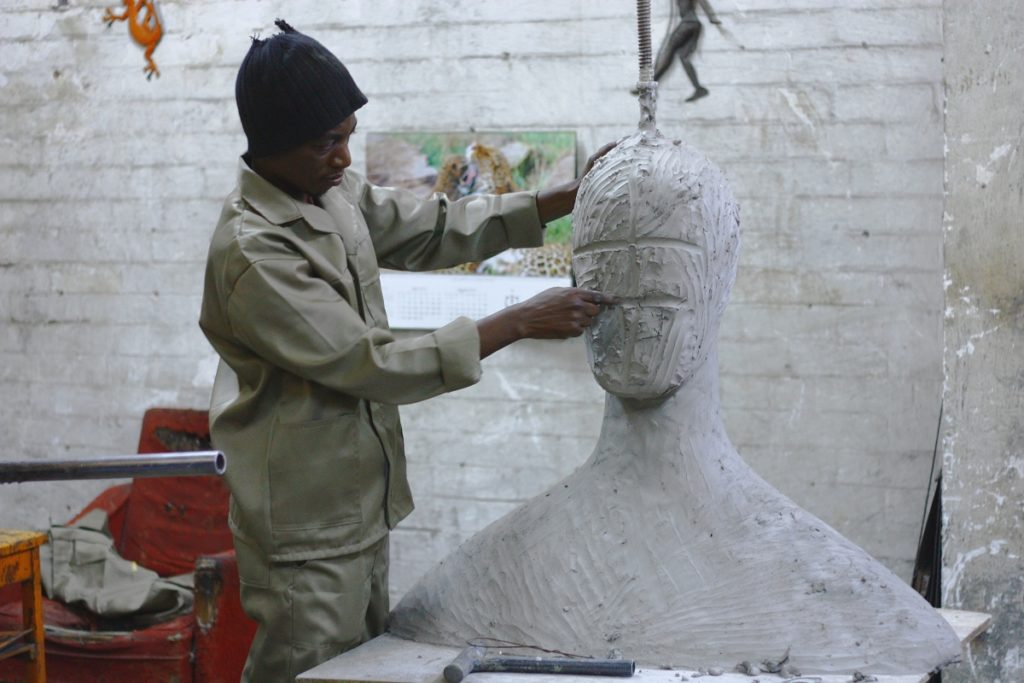 Black man in skull cap and beige clothes sculpting face of larger-than-life bust in white-bricked studio.