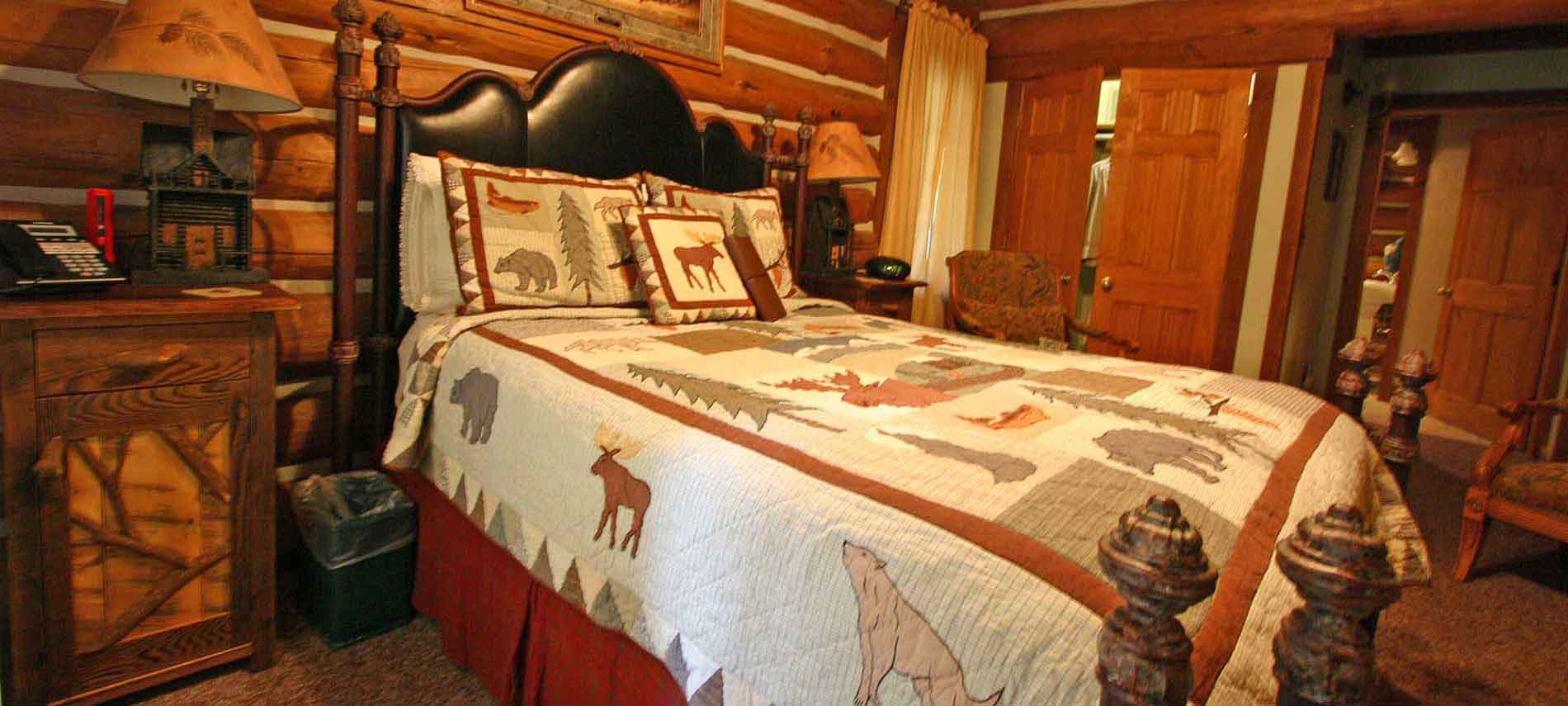 Westly Allen iron bed with a very rustic quilt with moose, bears and evergreens, along side hand crafted night stands. One wall is showing the logs in the wall and an accent chair
