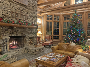 Large stone fireplace with warm fire, vaulted ceilings, cozy furniture and christmas tree