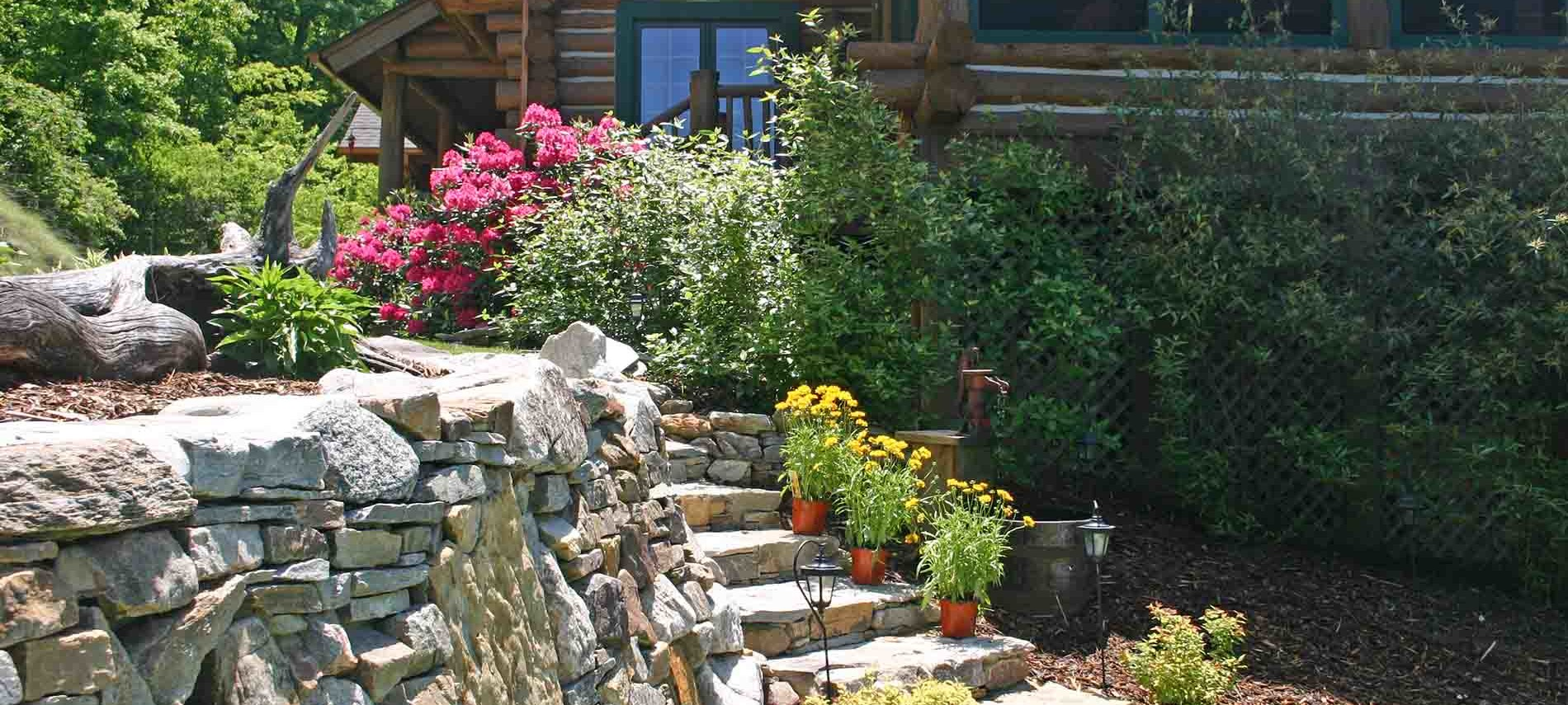 Yellow Flower Pots, one on each stip coming down stone steps  with Red Rhododendrons at the top