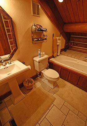 Bathroom with sloped ceiling, jacuzzi tub, and log beams