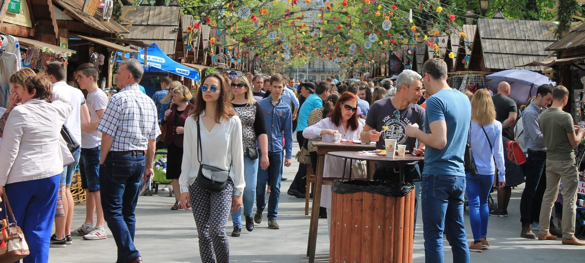 Street fair with people walking, eating at tables. Colorful decorations at top.