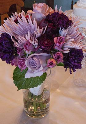 Brides bouquet with Pinks and purple on a table with partial view of the wedding cake