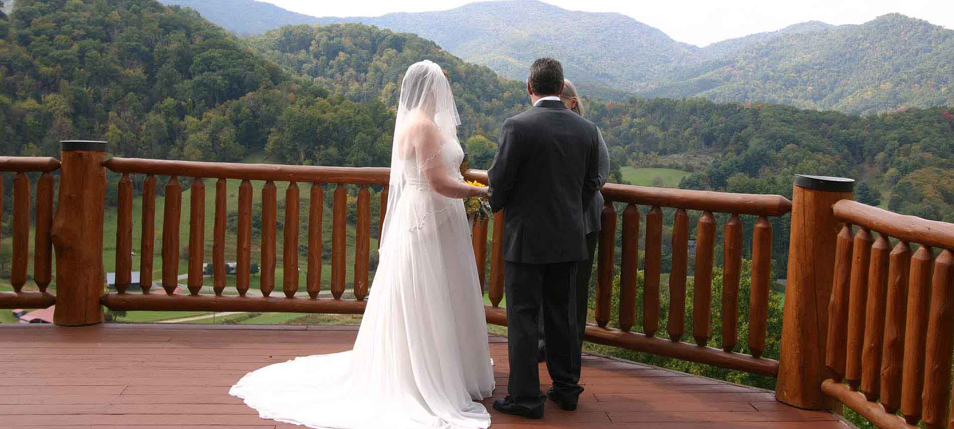 Wedding Couple with Minister on the back deck overlooking the mountains, Her wedding dress pops out in front of the Mountains Greens