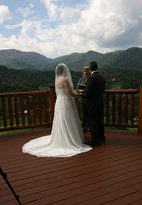 Wedding Couple with Minister on the back deck overlooking the mountains, Her wedding dress pops out in front of the Mountains Greens Great place to Elope