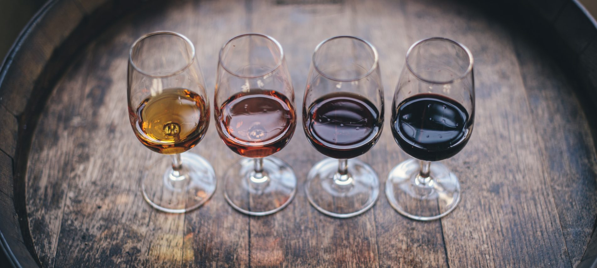 Four wine glasses on an oak barrel with a variety of wine