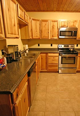 Light color wood cabinets with Stainless steel appliances and dark green counter tops. A perfect kitchen