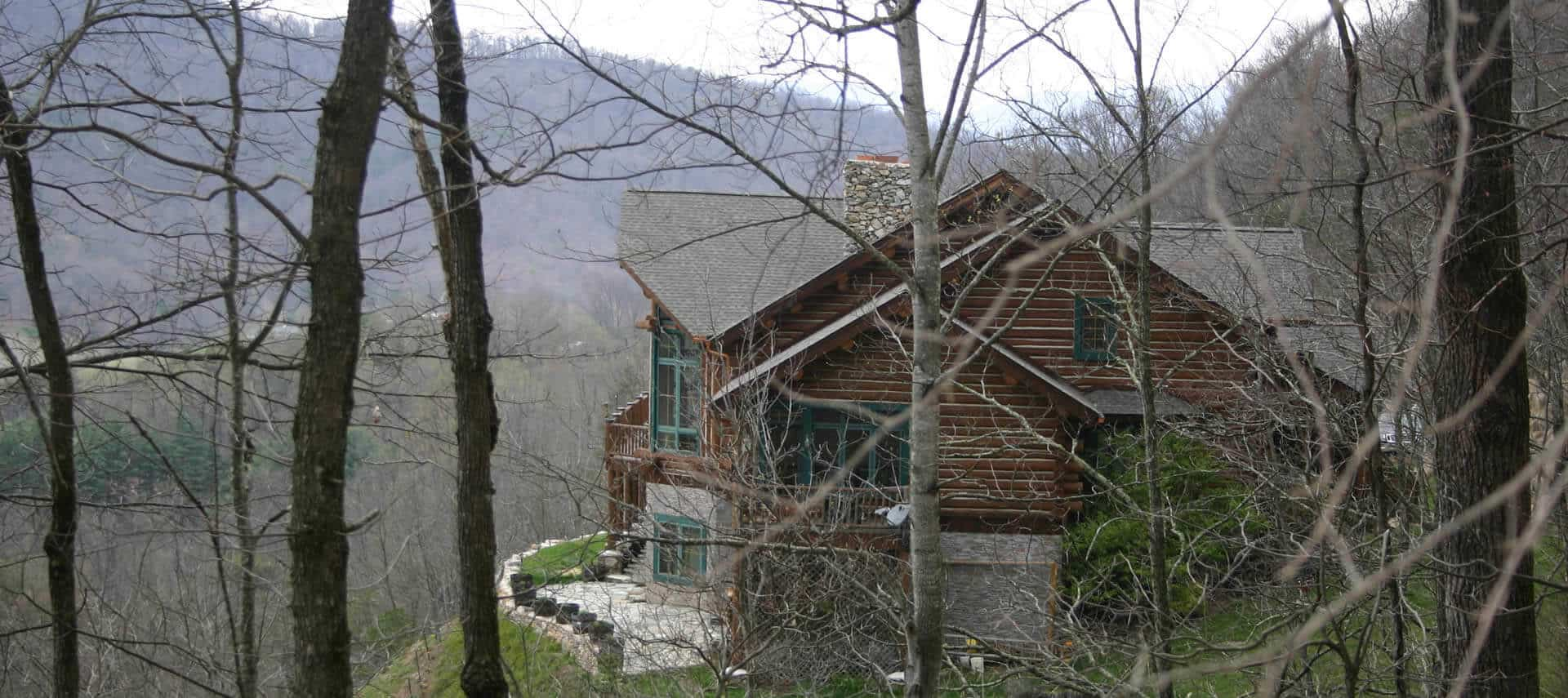 Side view through trees of large log-cabin home with a stone patio and stone lower level.