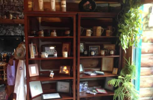Gift shop - two shelves filled with custom mugs, photos, candles, and other items for sale.