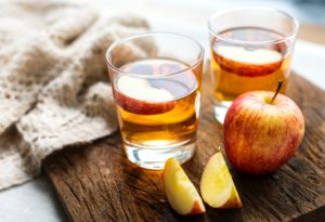 2 glass, short tumblers (old-fashioneds) with cider with apple slice in glass. Plus apple and apple slices next to glass on wooden tabletop.