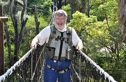 Ken with gray hair holding onto large rope bridge with harness and green trees behind