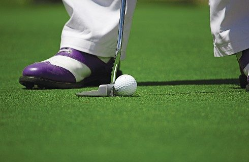 Legs of golfer with white pants and brown and white shoes with putter on green