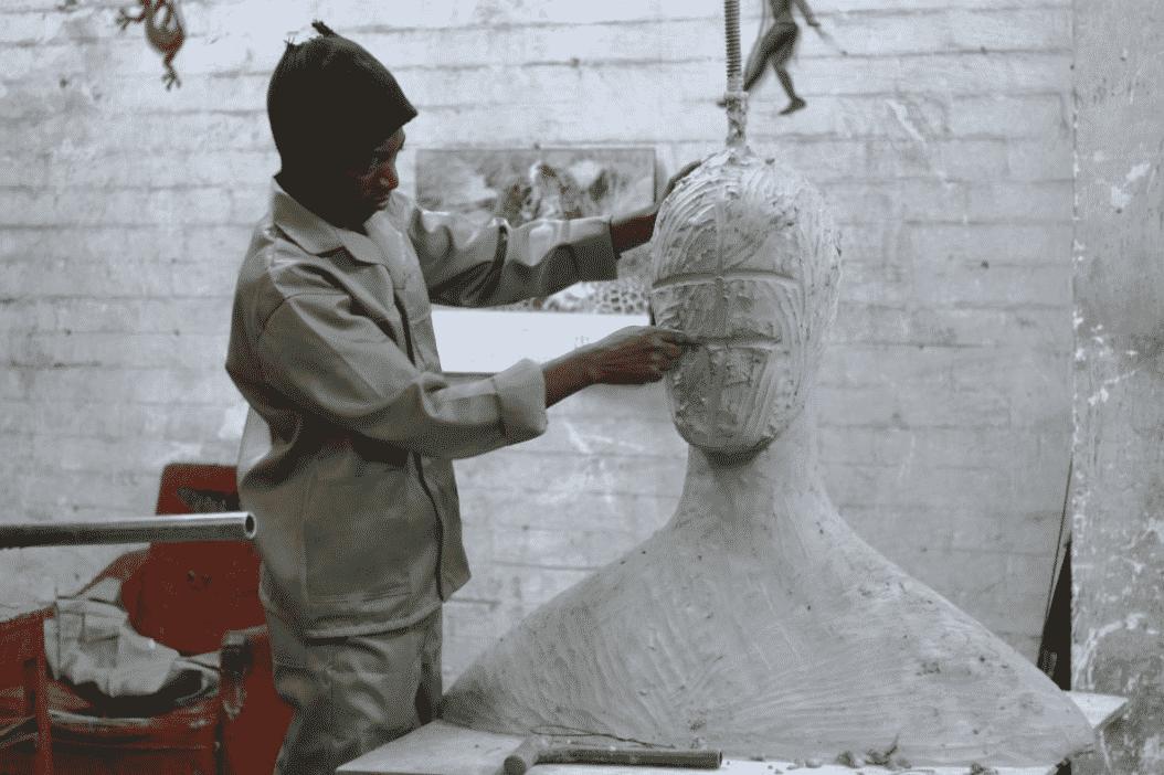 Man in art studio carving a sculpture