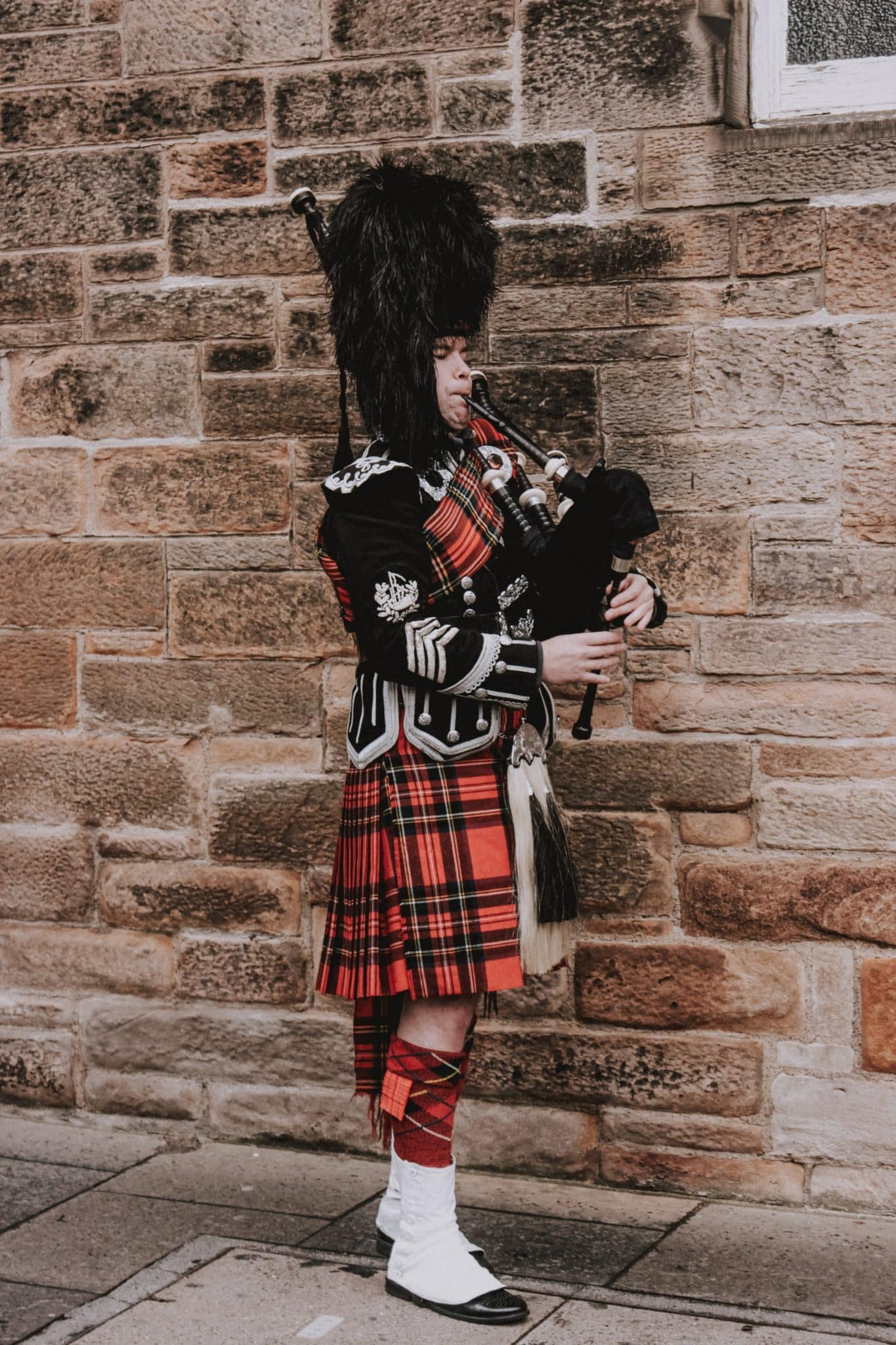 Male bagpiper dressed in Scottish garb with kilt