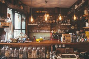 inside of a rustic bar, glasses, bottles, neatly organized.