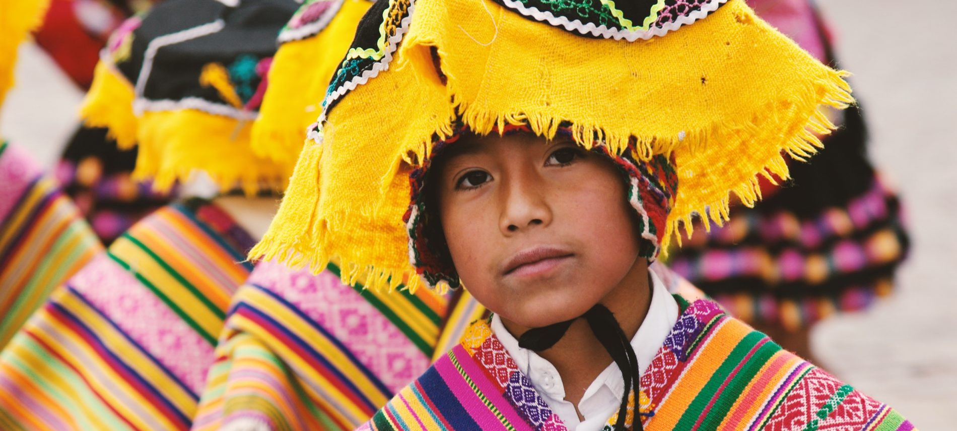 Mexican boy in yellow, green and black floppy head covering and colorful shawl. Similarly dressed figures behind him.