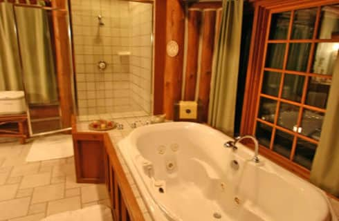 Whirlpool tub next to glass-walled shower in large bathroom tiled in beige with wood trim.