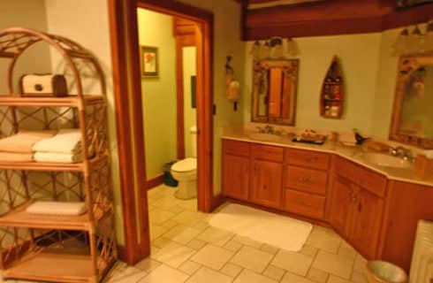 Expansive tiled bathroomw with a large, two-sink vanity and wooden beams in ceiling.