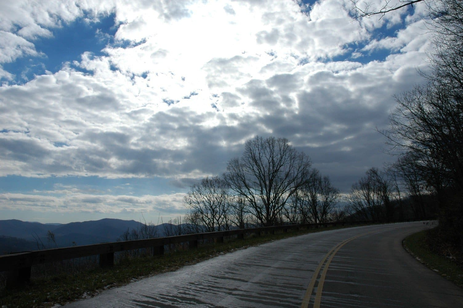 View from Blue Ridge Parkway of distant mountains amidst blue skies and white clouds
