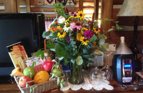 Pretty wildflowers in a glass vase next to a basket of fruit and snacks.