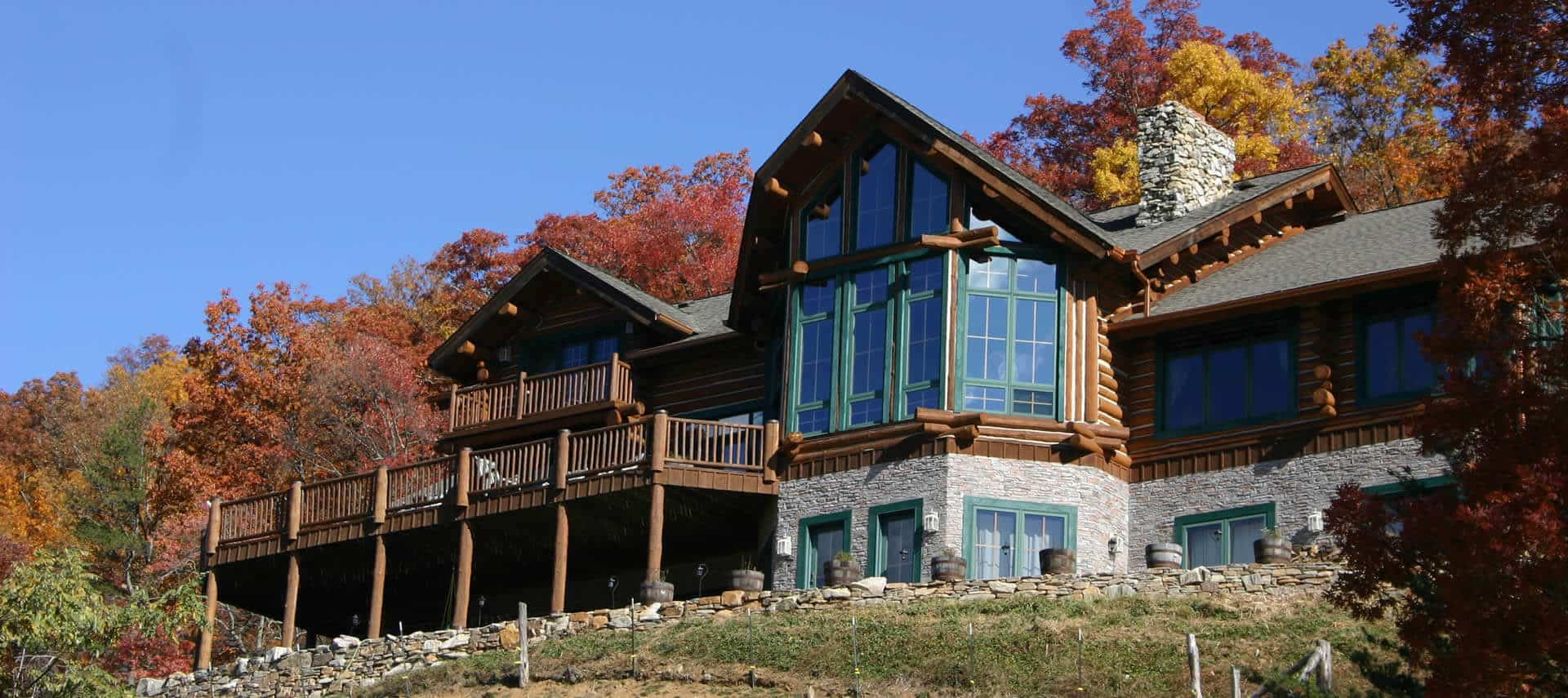 Large log-cabin style home with tall windows, stone walls on first floor, and second floor large deck.