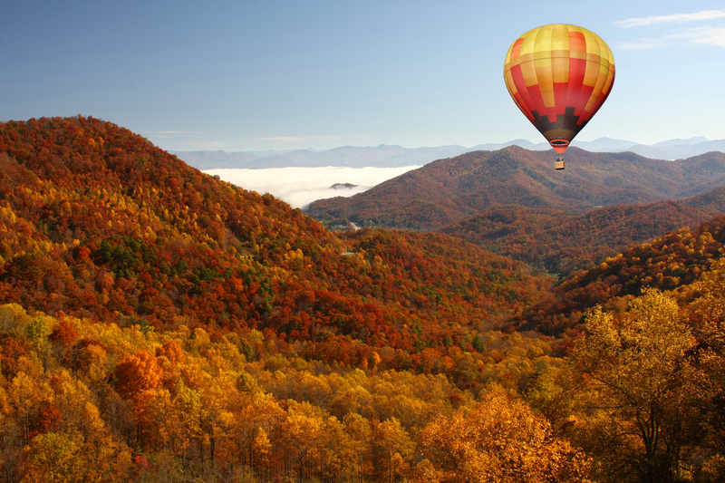 a yellow, orange, and brown hot air balloon flying over the smokey mountains and trees the same colors