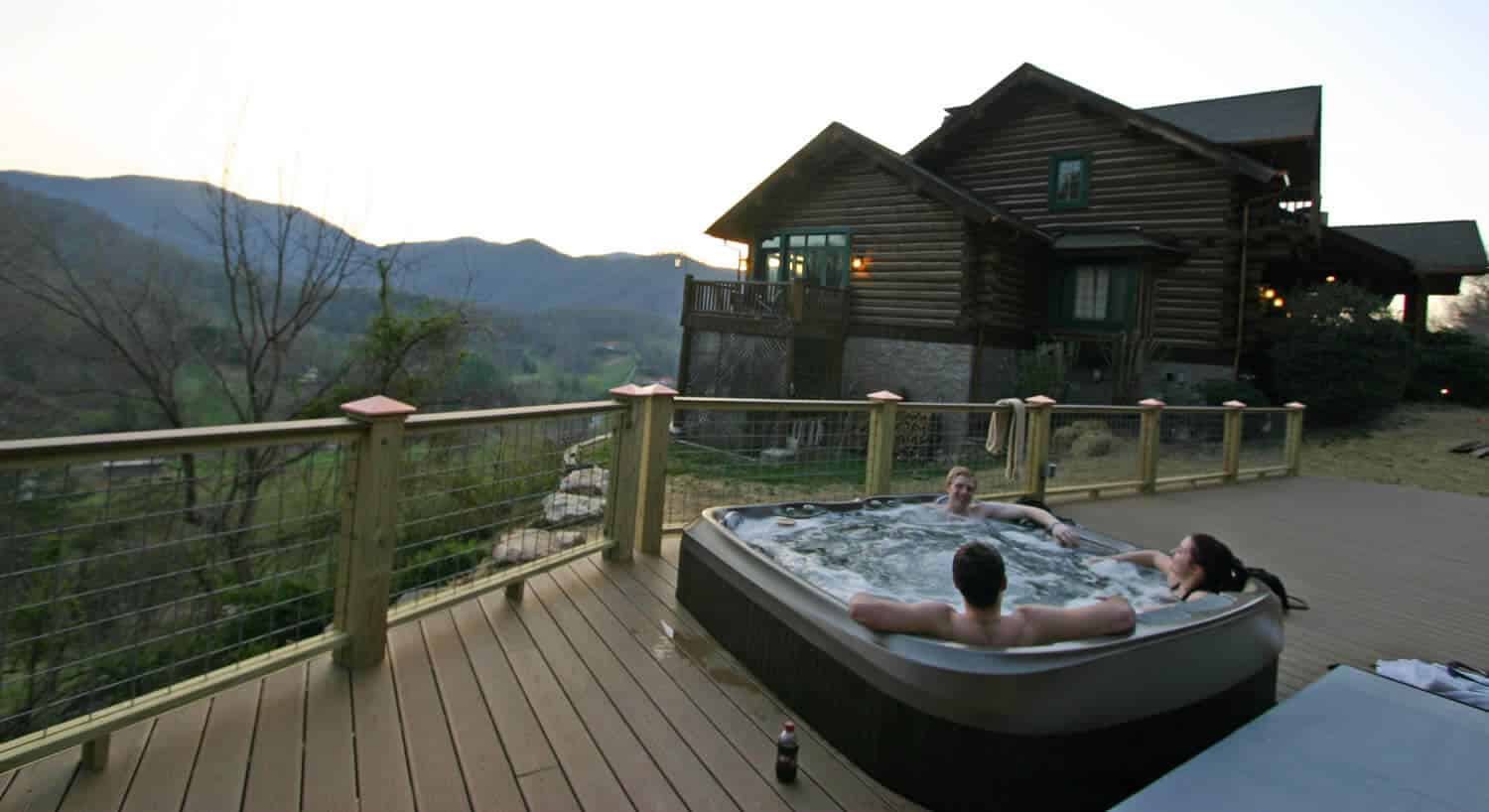 Three people enjoy a hot tub on a wooden deck next to a large log-cabin style home.