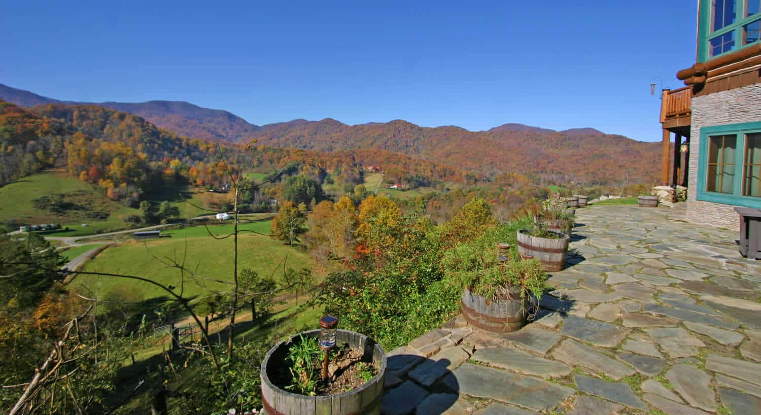 Stone patio overlooks a green valley and extended hills covered in fall foliage.