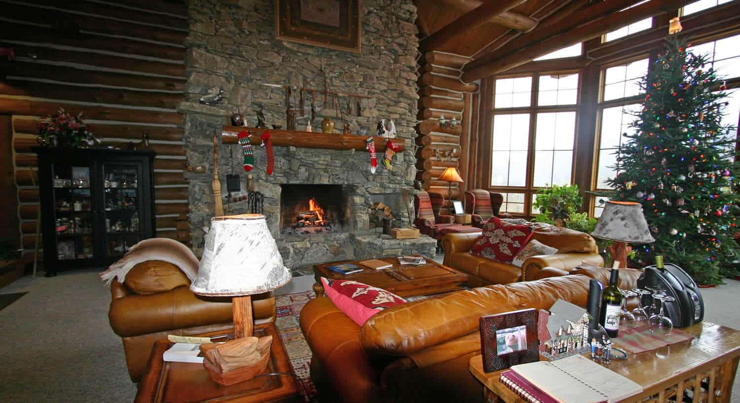 Large living room with stone fireplace decorated for Christmas.